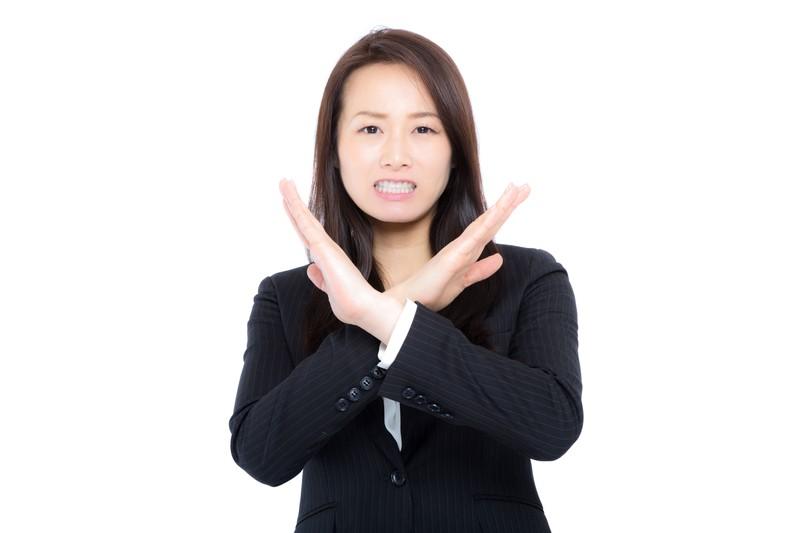 コーチングで目標達成出来ないのはダメと手でバッテンしている女性